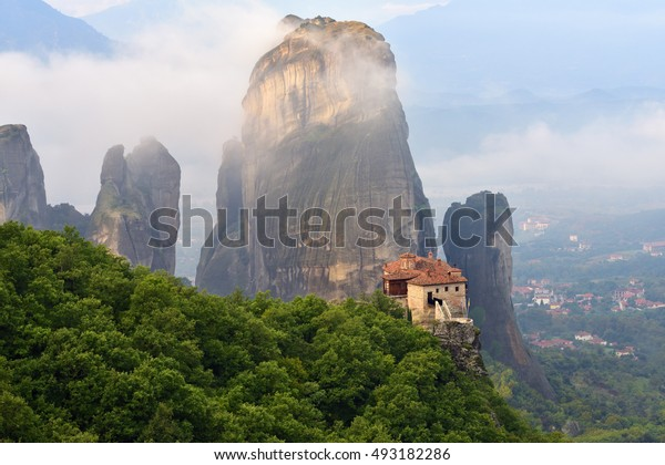 Meteora monasteries. Beautiful view on the Holy Monastery of Roussanov placed on the edge of high rock covered of the morning clouds and mist at sunrise, Kastraki, Greece