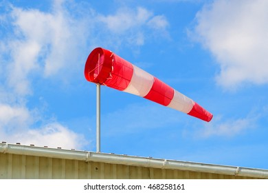 Meteorology windsock inflated by wind on the hangar roof. Red windsock indicate the direction and strength of the wind on airport.