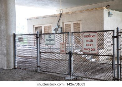 Meter room guarded by chain link fence and gate with a no trespassing, tow away zone and emergency access only sign