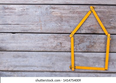 Meter rule folded in form of a house. House shape made from folding ruler on old wooden background. Space for text.