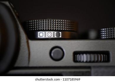 Metering dial of a digital camera in black background.