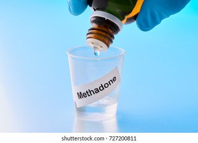 methadone is dropped into a beaker. The inscription on the mug is English