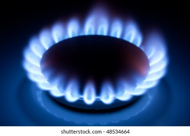 Methane blue flames at kitchen cooker in the dark