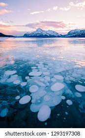 Methane Bubbles frozen in Abraham Lake in Clearwater County, near Nordegg, Alberta, Canada. Elliot Peak lit by the sunset in the background. Canadian Winter scene.