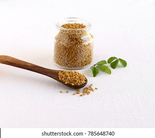 Methi or fenugreek seeds in a wooden spoon and in the background is a glass bottle of the same seeds and next to the bottle are methi leaves.