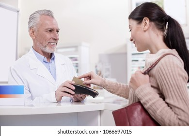 Method of payment. Appealing female client paying for drug while standing in profile