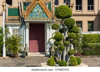 Meticulously trimmed trees with beautifully decorated door on the background. Bangkok, Thailand
