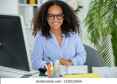 Metisse secretary working in office