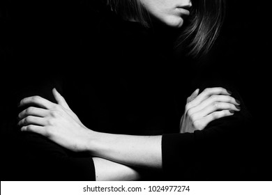 #metoo movement concept. Closeup portrait of young woman hiding face, posing with crossed hands, isolated on black background. Human emotion, expression, rights, communication. Text space. Studio shot