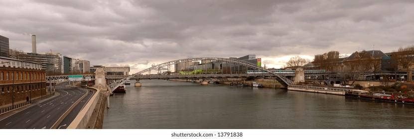 """Metro panorama on """"Pont de la Rapée"""" under a heavy dark sky in Paris"""