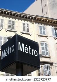 a Metro sign in Marseille, France with classic French architecture buildings with old wooden shutters on windows