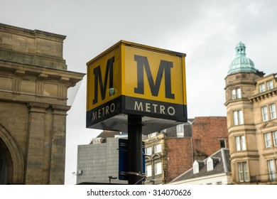 Metro sign on top of a post, in a street,  The weather is dreay and bleak.