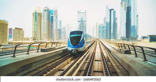 Metro train on Red line in Dubai downtown with skyscrapers at background.