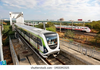 A metro train of Taichung MRT traveling thru a bridge near the High Speed Rail Station and a Puyuma Express train passing-by on the railway in the background, in Wuri District, Taichung City, Taiwan