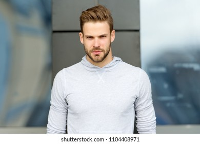 Metrosexual concept. Guy bearded and attractive cares about appearance. Man with bristle on serious face, urban background, defocused. Man with beard or unshaven guy looks handsome and cool