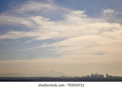 Metrotown skyline silhouette from a far distance, with a seaplane in the sky - Burnaby, Vancouver, Canada