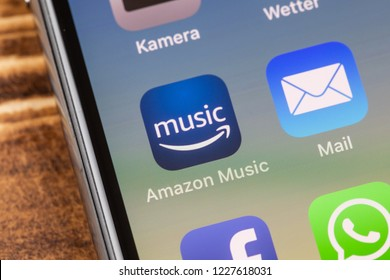 METTINGEN, GERMANY - NOVEMBER 9, 2018: Close up to amazon music app on the screen of an iPhone X with personalized background