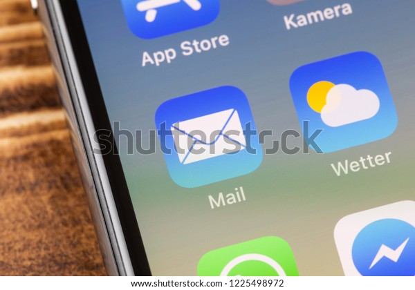 METTINGEN, GERMANY - NOVEMBER 9, 2018: Close up to Mail app on the screen of an iPhone X with personalized background