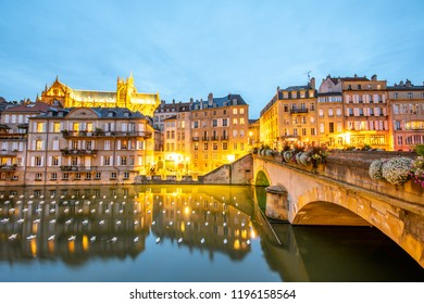 METZ, FRANCE - August 26, 2017: Night view on the riverside with beautiful illuminated buildings, bridge and cathedral on the background in Metz city in Lorraine region of France