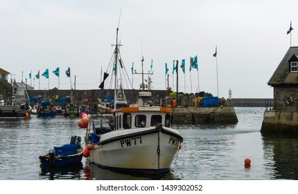 Mevagissey, Cornwall. England- June 26, 2019: The fishing boat Girl Rachel PW77, moored in the harbour, with entrance seawalls and other vessels, during the Fish Festival