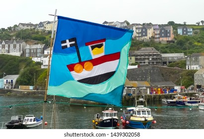 Mevagissey, Cornwall. England- June 26, 2019:  A flag celebrating the Annual Fish festival flies in wind over the harbour. With fishing boats at anchor and backdrop of the village.