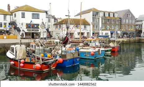 Mevagissey, Cornwall. England- June 26, 2019: Colourful charter boats and trawlers moored in the harbour during the annual Fish Festival. With background of the village to the skyline.