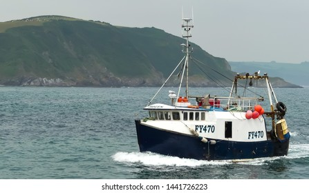 Mevagissey, Cornwall. England- June 26, 2019: The trawler Imogen FY470 returns to the harbour with its catch of fresh fish. Landscape image with space for text.