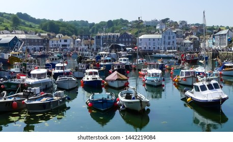Mevagissey, Cornwall. England- June 26, 2019: The bustling harbour of the village teems with both working and pleasure boats. All at anchor, looking back towards the quayside.