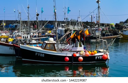 Mevagissey, Cornwall. England- June 26, 2019: The bustling harbour of the village teems with both working and pleasure boats. Vessels at anchor behind the sea wall.