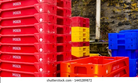 Mevagissey, Cornwall. England- June 26, 2019: The colourful stacked plastic catch trays, waiting for trawlers' Imogen and Likely Lad to fill with fish.  Outside on the Quay.
