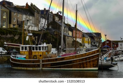 Mevagissey, Cornwall. England- September 27, 2019: The traditional working harbour, with moored, wooden and other fishing boats. Highlighted in autumn by a rainbow over the village houses.