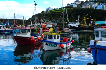 Mevagissey, Cornwall. England - September 27, 2019: The working fishing boats moored in harbour provide a colourful attraction for tourists.
