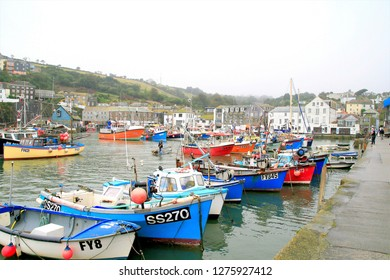 Mevagissey, Cornwall, UK. October 05, 2015. Holidaymakers and locals enjoying the colorful harbor on a October overcast day at Mevagissey in Cornwall, UK.