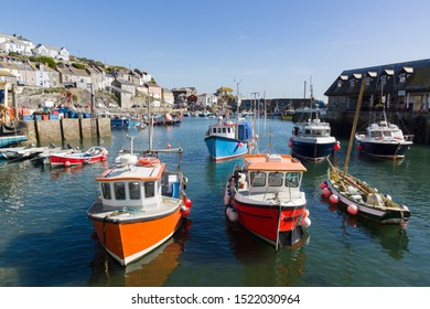 Mevagissey harbour in Cornwall England with colorful fishing boats at anchor