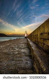 Mevagisseys harbour wall and lighthouse bathed in the golden hour sun as last light draws nearer.