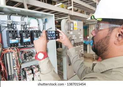Mexicali, Baja California/Mexico. Oct 29 2018: Electric technician taking a photo of circuit breakers using a cel phone, inside electric control panel as maintenance procedure.
