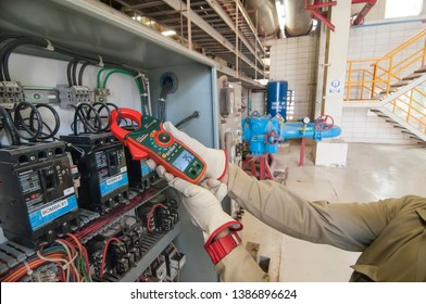 Mexicali, Baja California/Mexico Oct 29-2018 : Geothermal power plant, electric technician is measuring electric current in amps, with  clamp meter as part daily electric panel inspection.