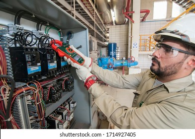 Mexicali, Baja California/Mexico> Oct-29-2018, Mexican electric technician performing Maintenance to an electric control motor panel in the geothermal power industry. skilled jobs apprentice program.