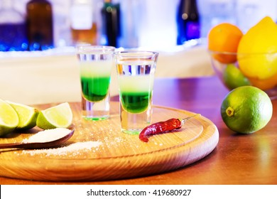Mexican alcoholic cocktail drinks shot on a wooden board. Good tequila cocktail drinks, booze with decor composition with citrus fruits. Different layers of alcohol vodka, liqueur, chasers for drinks.