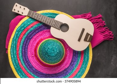 Mexican background. Sombrero, guitar and blankets on rustic slate background. Top view with copy space