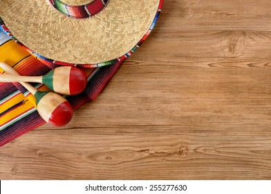 Mexican background, sombrero, maracas on wood.