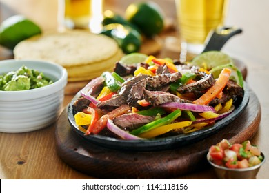 mexican beef fajitas in iron skillet with guacamole and beer