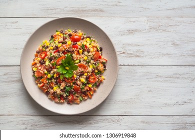 Mexican black bean corn quinoa salad on the wood white table. Top view.