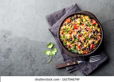 Mexican black bean corn quinoa salad in clay bowl top view, copy space.