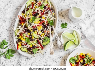 Mexican black bean salad. Salad with corn, beans, avocado and tortilla. On a light background, top view