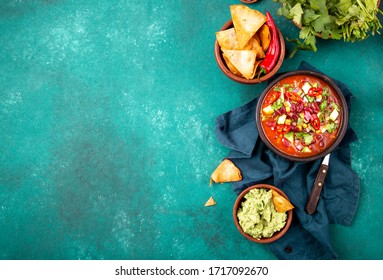 Mexican black bean soup with tomato, avocado and totopos. Blue background, top view.