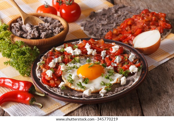 Mexican breakfast: huevos rancheros close-up on a plate on the table. horizontal