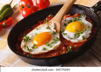 Mexican breakfast huevos rancheros: fried egg with salsa closeup in the pan. Horizontal