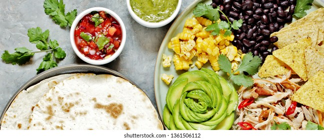 Mexican Buddha bowl with chicken meat fiber, black beans, corn, avocado rose, nachos corn chips. served with avocado sauce (avocado mayonnaise) and tomato salsa (Pico de Gallo) and tortillas