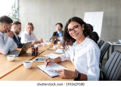 Mexican Businesswoman Posing Taking Notes And Smiling To Camera Sitting At Corporate Business Meeting With Coworkers In Office. Female Entrepreneurship Career Concept
